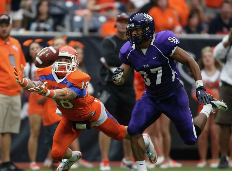 Sam Houston State's Trey Diller (left) makes a leaping 39-yard reception past SFA's Josh Aubrey during the first half of the Battle of the Piney Woods college football game, Saturday, October 6, 2012 at Reliant Stadium in Houston, TX. Photo: Eric Christian Smith, For The Chronicle
