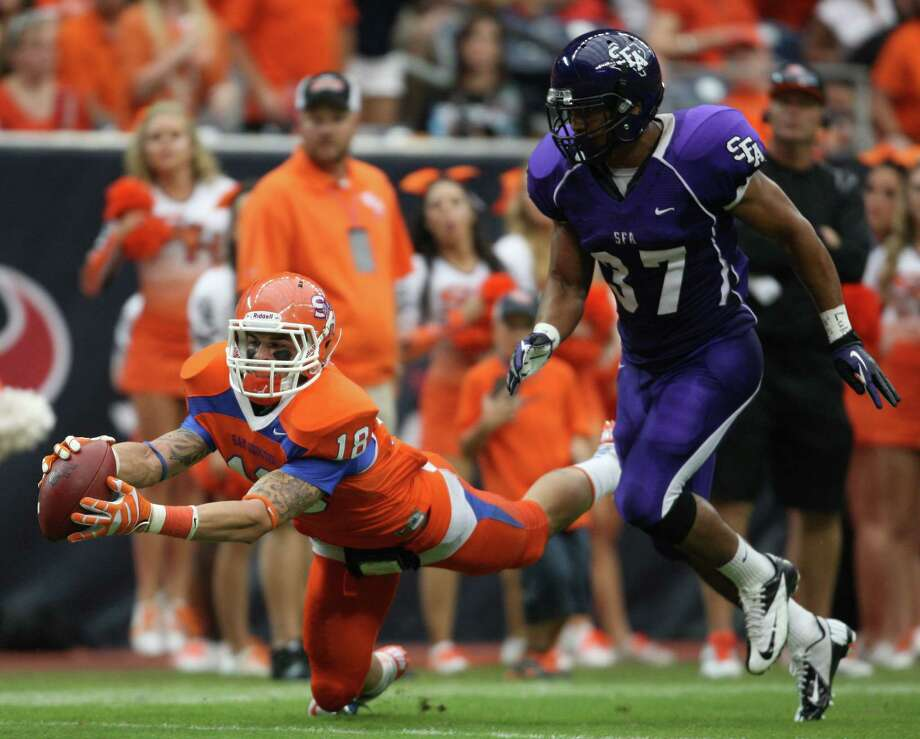 Sam Houston State's Trey Diller (left) makes a leaping 39-yard reception past SFA's Josh Aubrey during the first half. Photo: Eric Christian Smith, For The Chronicle