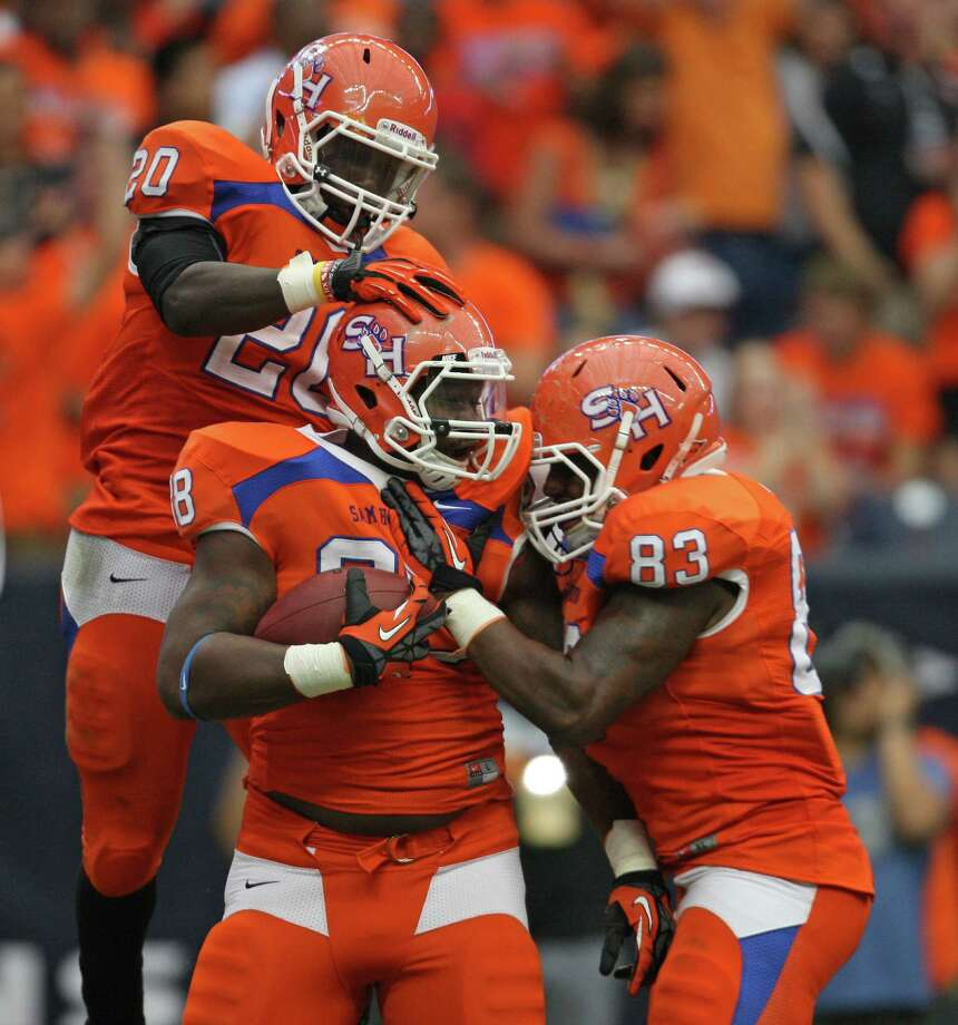 Sam Houston State's K.J. Williams (88) celebrates his touchdown reception with Tim Flanders (20) and T.J. Jones during the first half of the Battle of the Piney Woods college football game against SFA, Saturday, October 6, 2012 at Reliant Stadium in Houston, TX. Photo: Eric Christian Smith, For The Chronicle