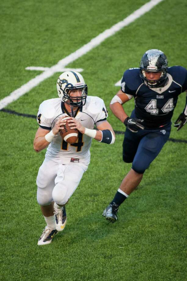 Cypress Ranch quarterback Cole Martin (14) is chased out of the pocket by Cypress Ridge defensive tackle Mark Velazquez during the first quarter of a high school football game at Pridgeon Stadium on Saturday, Oct. 6, 2012, in Houston. Photo: Andrew Richardson, For The Chronicle / © 2012 Andrew Richardson