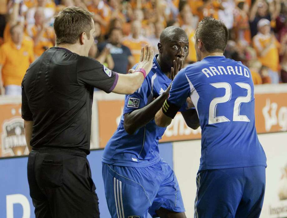 HOUSTON, TX - OCTOBER 06: Linesman Jason Callum has words with Hassoun Camara #6 and Davy Arnaud #22 of the Montreal Impact after Brian Ching #25 of the Houston Dynamo apparently scored the go ahead goal in extra time against the Montreal Impact at BBVA Compass Stadium on October 6, 2012 in Houston, Texas. The goal was later reversed. Montreal and Houston played to 1-1 tie. Photo: Bob Levey, Getty Images / 2012 Getty Images