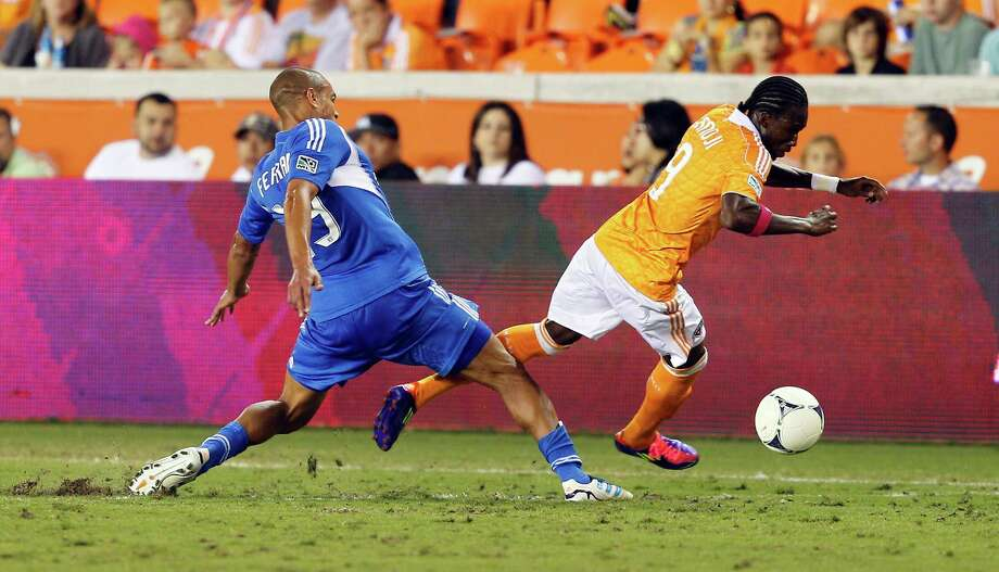HOUSTON, TX - OCTOBER 06: Macoumba Kandji #9 of the Houston Dynamo is tripped up by Matteo Ferrari #13 of the Montreal Impact in the second half at BBVA Compass Stadium on October 6, 2012 in Houston, Texas. Montreal and Houston played to 1-1 tie. Photo: Bob Levey, Getty Images / 2012 Getty Images