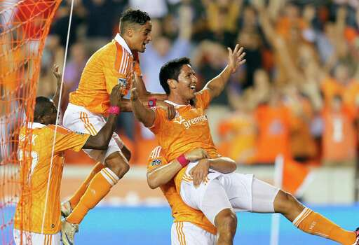 HOUSTON, TX - OCTOBER 06:  Brian Ching #25 of the Houston Dynamo celebrates with Calen Carr #3 and Boniek Garcia #27 after what he thought was the go ahead goal in extra time against the Montreal Impact at BBVA Compass Stadium on October 6, 2012 in Houston, Texas. The goal was later reversed as the linesman said Ching was offside on the play. Montreal and Houston played to 1-1 tie. Photo: Bob Levey, Getty Images / 2012 Getty Images