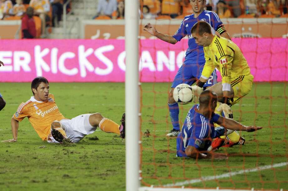 HOUSTON, TX - OCTOBER 06:  Brian Ching #25 of the Houston Dynamo has his shot on goal stopped by goalkeeper Troy Perkins #1 of the Montreal Impact in the second half at BBVA Compass Stadium on October 6, 2012 in Houston, Texas. Montreal and Houston played to 1-1 tie. Photo: Bob Levey, Getty Images / 2012 Getty Images