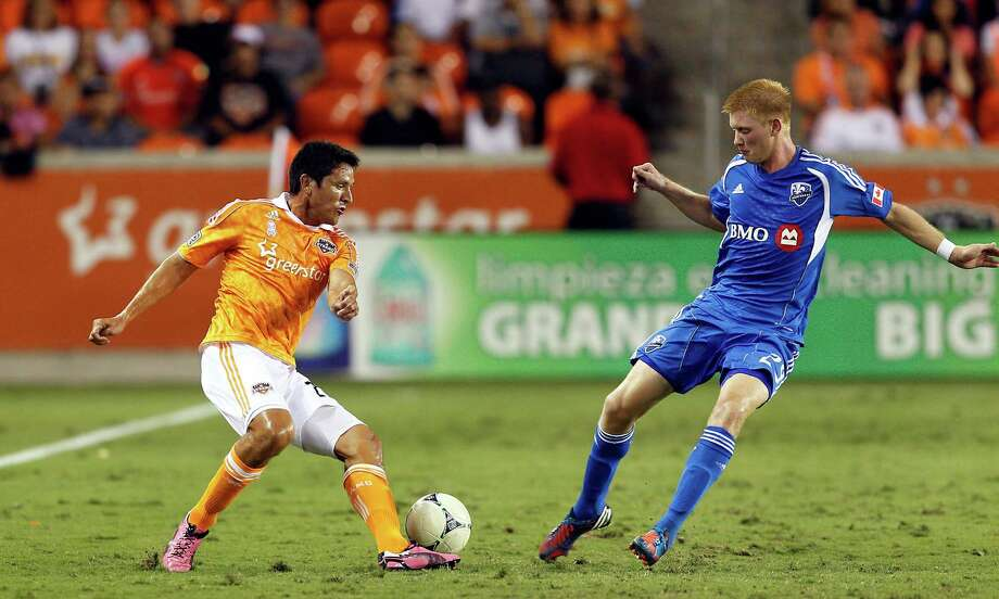 HOUSTON, TX - OCTOBER 06:  Brian Ching #25 of the Houston Dynamo attempts elude Calum Mallace #29 of the Montreal Impact at BBVA Compass Stadium on October 6, 2012 in Houston, Texas. Montreal and Houston played to 1-1 tie. Photo: Bob Levey, Getty Images / 2012 Getty Images