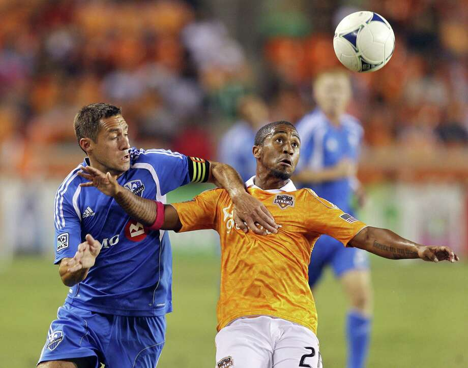 HOUSTON, TX - OCTOBER 06: Corey Ashe #26 of the Houston Dynamo and Davy Arnaud #22 of the Montreal Impact fight for possesion at BBVA Compass Stadium on October 6, 2012 in Houston, Texas. Photo: Bob Levey, Getty Images / 2012 Getty Images