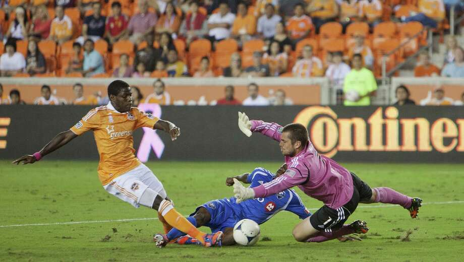 HOUSTON, TX - OCTOBER 06: Tally Hall #1 of the Houston Dynamo makes a save on a shot by Sanna Nyassi #11 of the Montreal Impact as Kofi Sarkodie #8 of the Houston Dynamo looks for any rebounds at BBVA Compass Stadium on October 6, 2012 in Houston, Texas. Photo: Bob Levey, Getty Images / 2012 Getty Images
