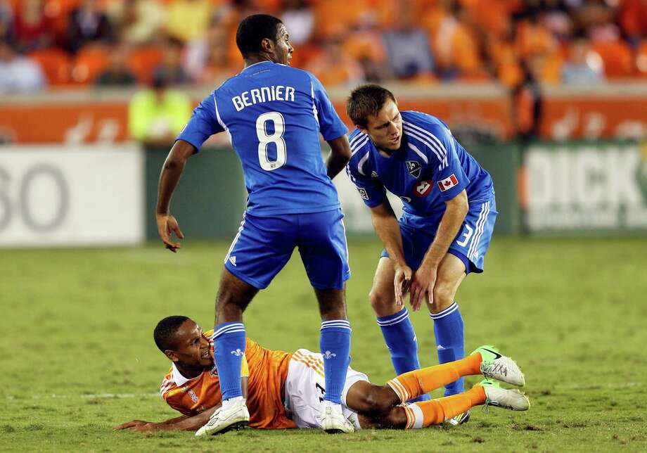 HOUSTON, TX - OCTOBER 06:  Ricardo Clark #13 of the Houston Dynamo lays on the pitch between Patrice Bernier #8 and Andrew Wenger #33 of the Montreal Impact at BBVA Compass Stadium on October 6, 2012 in Houston, Texas. Montreal and Houston played to 1-1 tie. Photo: Bob Levey, Getty Images / 2012 Getty Images