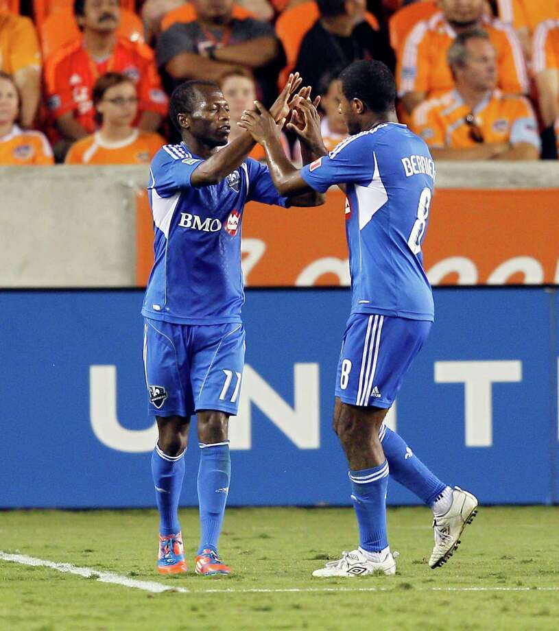 HOUSTON, TX - OCTOBER 06:  Sanna Nyassi #11 and Patrice Bernier #8 of the Montreal Impact celebrate Nyassi's goal in the second half against the Houston Dynamo at BBVA Compass Stadium on October 6, 2012 in Houston, Texas. Montreal and Houston played to 1-1 tie. Photo: Bob Levey, Getty Images / 2012 Getty Images