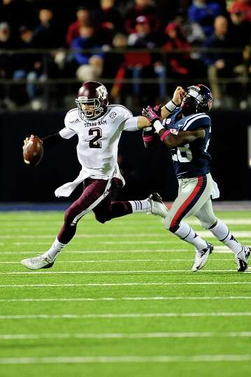 OXFORD, MS - OCTOBER 06: Johnny Manziel #2 of the Texas A&M Aggies stiff arms LaKedrick King #28 of