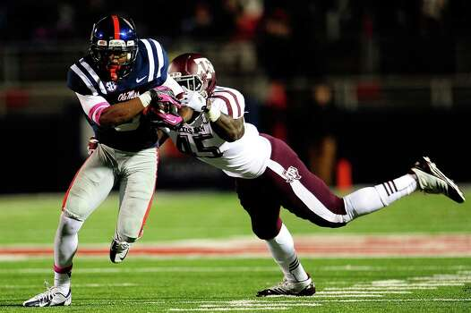 OXFORD, MS - OCTOBER 06: Jeff Scott #3 of the Ole Miss Rebels breaks a tackle by Steven Jenkins #45 of the Texas A&M Aggies during a game at Vaught-Hemingway Stadium on October 6, 2012 in Oxford, Mississippi. Photo: Stacy Revere, Getty Images / 2012 Getty Images