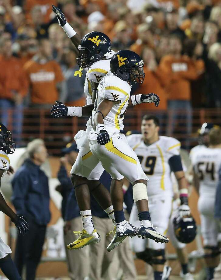 AUSTIN, TX - OCTOBER 06:  (L-R) KJ Myers #19 and Dustin Brown #23 of the West Virginia Mountaineers celebrate on the field during a game against the Texas Longhorns at Darrell K Royal-Texas Memorial Stadium on October 6, 2012 in Austin, Texas. Photo: Ronald Martinez, Getty Images / 2012 Getty Images