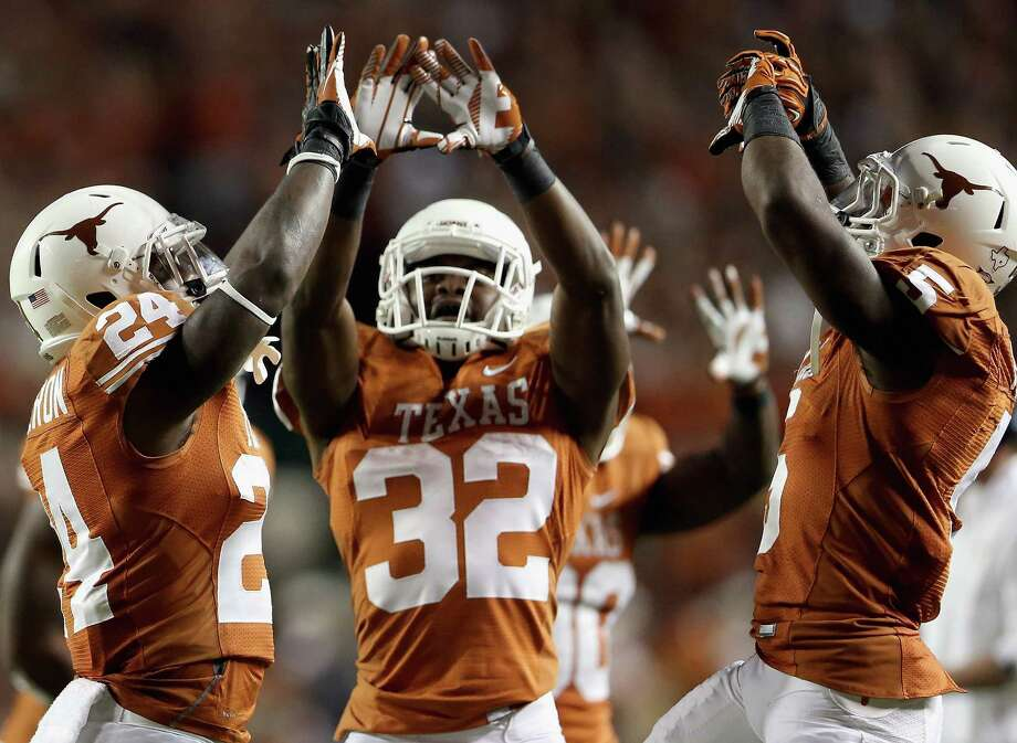 AUSTIN, TX - OCTOBER 06:  (L-R) Joe Bergeron #24, Johnathan Gray #32 and Jeremy Hills #5 of the Texas Longhorns celebrate a touchdown against the West Virginia Mountaineers at Darrell K Royal-Texas Memorial Stadium on October 6, 2012 in Austin, Texas. Photo: Ronald Martinez, Getty Images / 2012 Getty Images