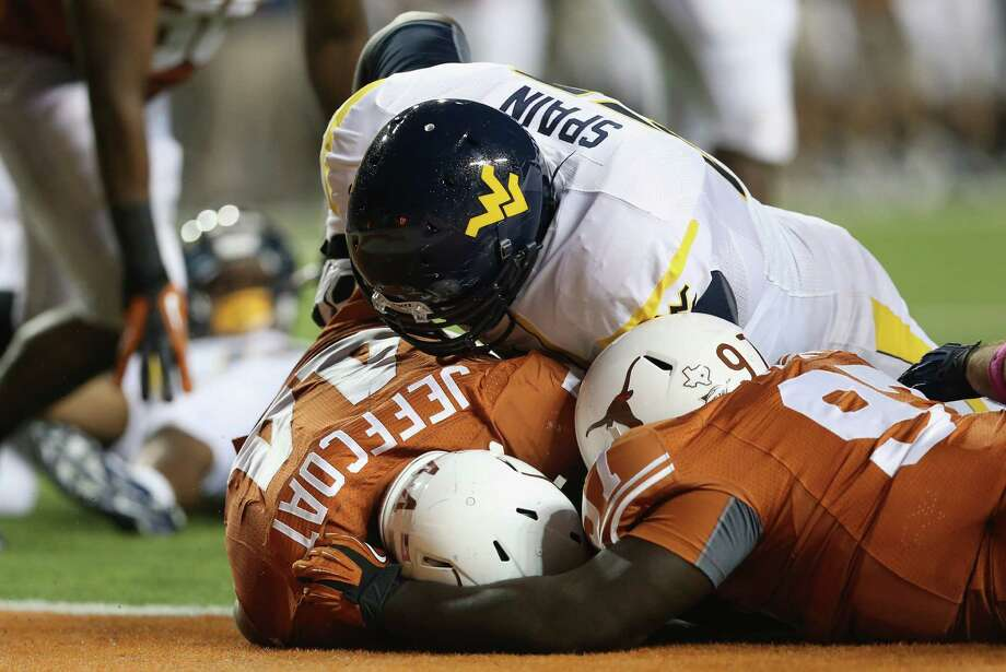 AUSTIN, TX - OCTOBER 06:  Jackson Jeffcoat #44 of the Texas Longhorns makes a touchdown fumble recovery against Quinton Spain #67 of the West Virginia Mountaineers at Darrell K Royal-Texas Memorial Stadium on October 6, 2012 in Austin, Texas. Photo: Ronald Martinez, Getty Images / 2012 Getty Images