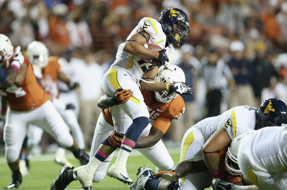 AUSTIN, TX - OCTOBER 06:  Andrew Buie #13 of the West Virginia Mountaineers is tackled by Steve Edmond #33 of the Texas Longhorns at Darrell K Royal-Texas Memorial Stadium on October 6, 2012 in Austin, Texas. Photo: Ronald Martinez, Getty Images / 2012 Getty Images