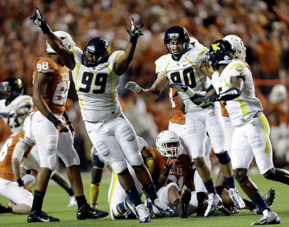 West Virginia's Desmond Jackson (99) and his teammates jump for joy after Texas kicker Anthony Fera pushed a 41-yard field-goal attempt wide right during the fourth quarter of Saturday night's game in Austin. Photo: Eric Gay / AP