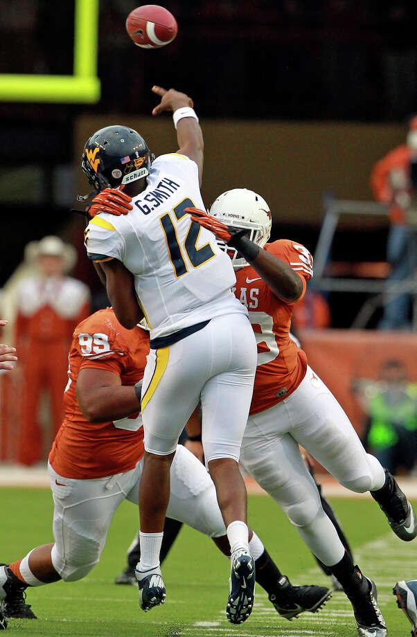 West Virginia quarterback  Geno Smith stands tall despite pressure from UT linebacker Steve Edmond. Photo: Tom Reel / ©2012 San Antono Express-News