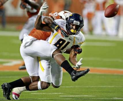 Mountaineer receiver J.D. Woods gets the ball knocked away by Qundre Diggs as Texas hosts West Virginia at Darrel K. Royal Texas Memorial Stadium in Austin on October 6, 2012. (San Antonio Express-News)