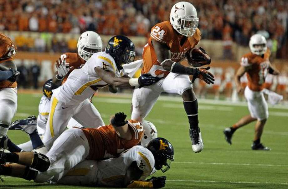 Longhorn running back Joe Bergeron flies over tacklers inthe second half as Texas hosts West Virginia at Darrel K. Royal Texas Memorial Stadium in Austin on October 6, 2012. (San Antonio Express-News)