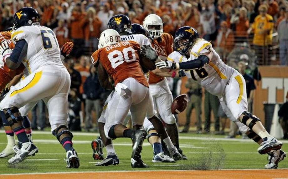 Longhorn defender Alex Okafor pressures Geno Smith and knocks the ball loose to be recovered by teammates for a touchdown as Texas hosts West Virginia at Darrel K. Royal Texas Memorial Stadium in Austin on October 6, 2012. (San Antonio Express-News)