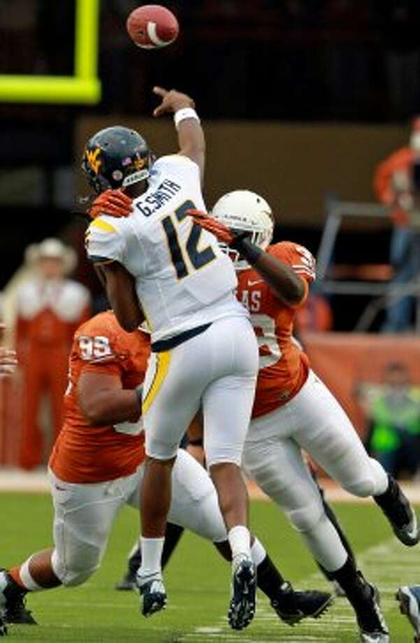 Geno Smith gets heavy pressure from Longhorn linebacker Steve Edmond in the first quarter as Texas hosts West Virginia at Darrel K. Royal Texas Memorial Stadium in Austin on October 6, 2012. (San Antonio Express-News)