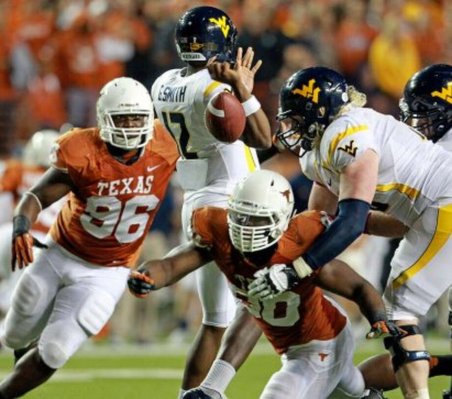 Longhorn defender Alex Okafor (80) knocks the ball loose from Geno Smith in the fourth quarter as Texas hosts West Virginia at Darrel K. Royal Texas Memorial Stadium in Austin on October 6, 2012. (San Antonio Express-News)
