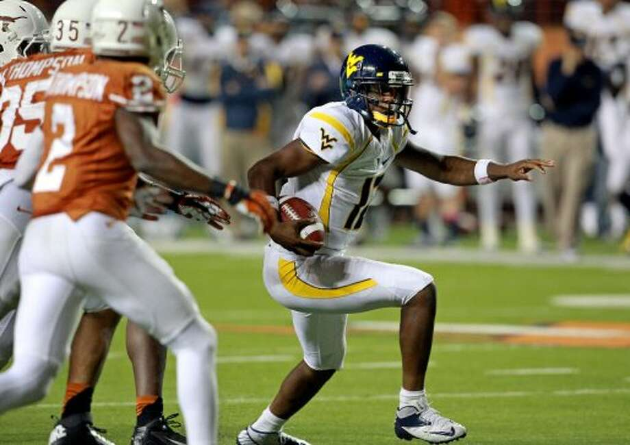 Geno Smith runs away from the Texas defense as Texas hosts West Virginia at Darrel K. Royal Texas Memorial Stadium in Austin on October 6, 2012. (San Antonio Express-News)