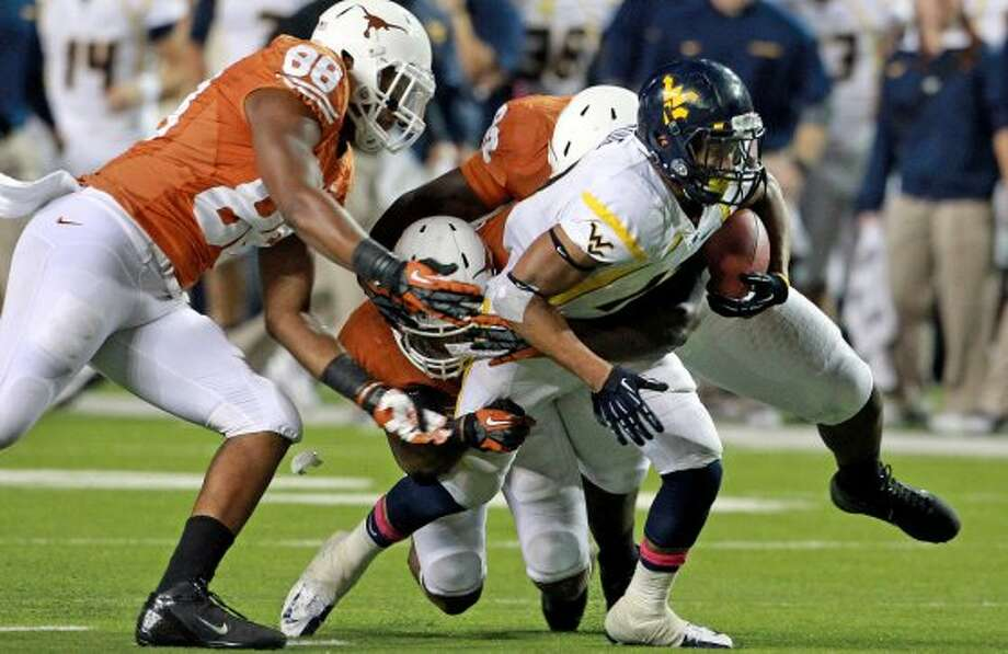 A trio of Longhorn defenders catches up to Andrew Buie as Texas hosts West Virginia at Darrel K. Royal Texas Memorial Stadium in Austin on October 6, 2012. (San Antonio Express-News)