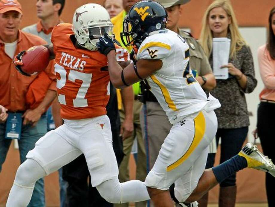 Daje Johnson gets caught by the facemask by Darwin Cook on a breakaway as Texas hosts West Virginia at Darrel K. Royal Texas Memorial Stadium in Austin on October 6, 2012. (San Antonio Express-News)