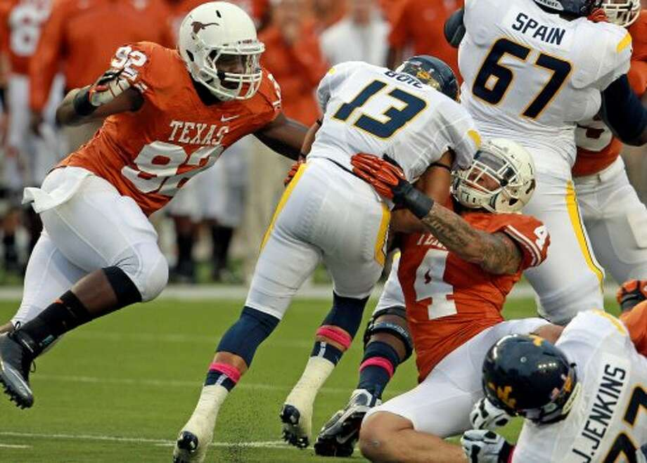 Reggie Wilson (92) and Kenny Vaccaro get a stop at the line of Andrew Buie as Texas hosts West Virginia at Darrel K. Royal Texas Memorial Stadium in Austin on October 6, 2012. (San Antonio Express-News)