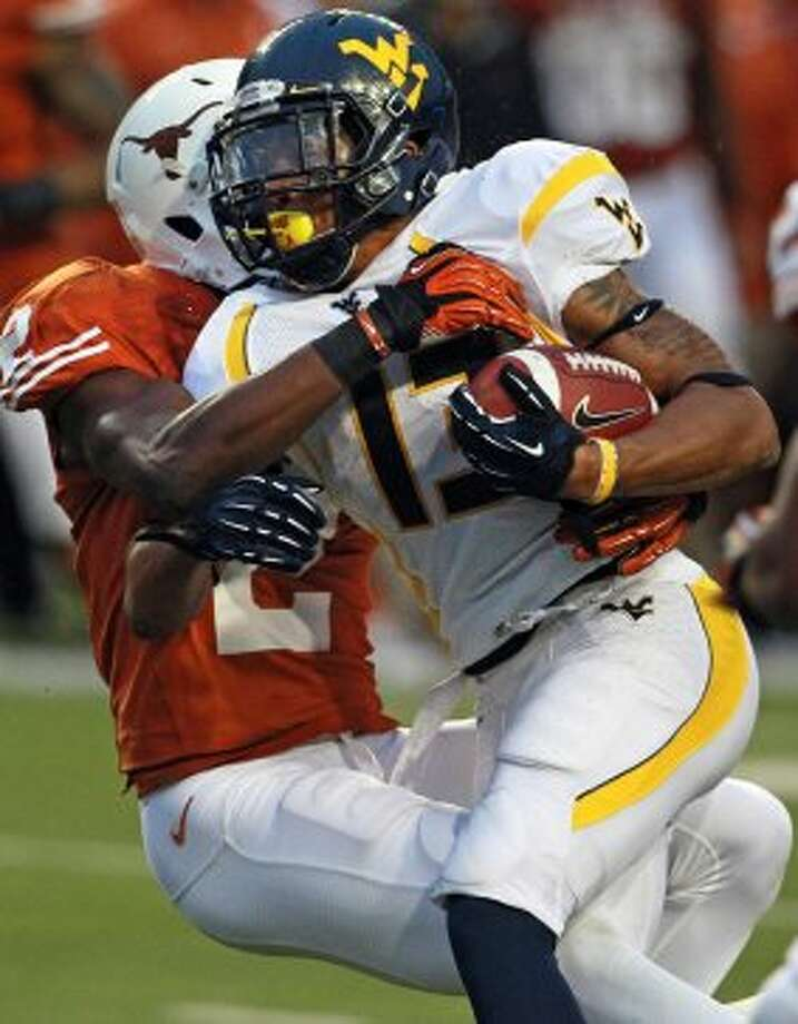 Mountaineer running back Andrew Buie plows into Mykkele Thompson as Texas hosts West Virginia at Darrel K. Royal Texas Memorial Stadium in Austin on October 6, 2012. (San Antonio Express-News)
