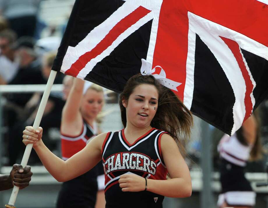 A Churchill cheerleader carries the Union Jack after a touchdown against MacArthur during high school football action at Comalander Stadium on Saturday, Oct. 6, 2012. Photo: Billy Calzada, Express-News / © San Antonio Express-News