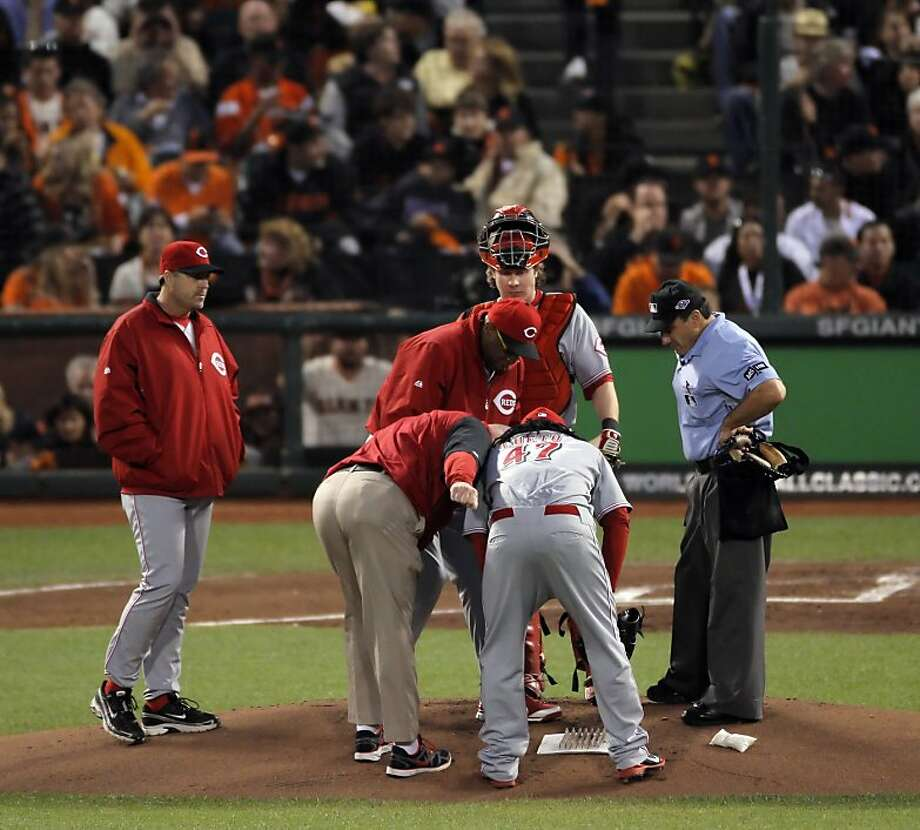 Manager Dusty Baker and the Reds' trainer check out injured starting pitcher Johnny Cueto, who left in the first inning. Photo: Carlos Avila Gonzalez, The Chronicle
