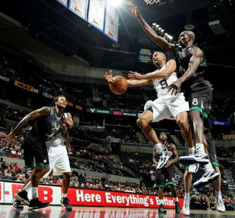San Antonio Spurs' Tony Parker is fouled by Montepaschi Siena's Benjamin Eze as Montepaschi Siena's David Ross looks on during first half action Saturday Oct. 6, 2012 at the AT&T Center. (San Antonio Express-News)