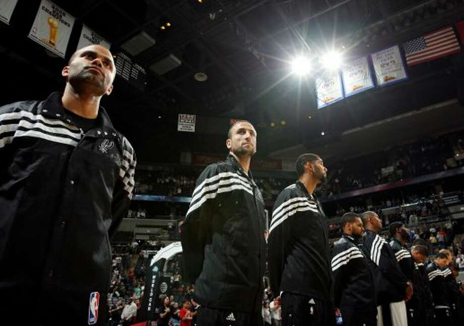San Antonio Spurs' Tony Parker (from left), Manu Ginobili, Tim Duncan and others stand during the national anthem before the game with Montepaschi Siena Saturday Oct. 6, 2012 at the AT&T Center. (San Antonio Express-News)