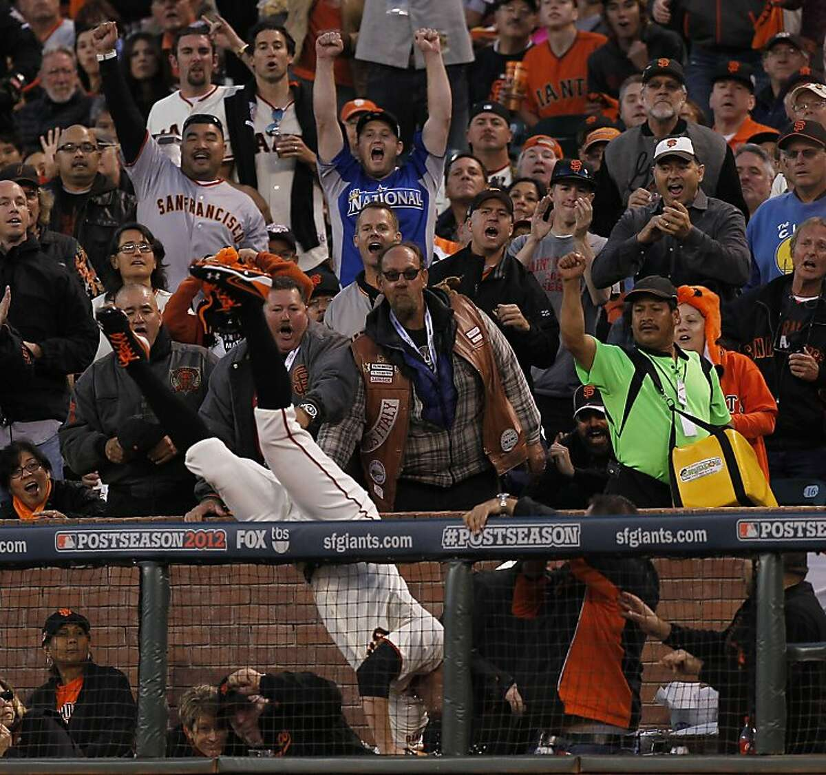 Giants first baseman Brandon Belt falls over the rail and into the crowd as he catches a pop fly ball hit by Reds' Zack Cozart, for an out in the first inningas the San Francisco GIants take on the Cincinnati Reds in game one of the National League Divisional Series at AT&T Park San Francisco, Calif., on Saturday October 6, 2012.