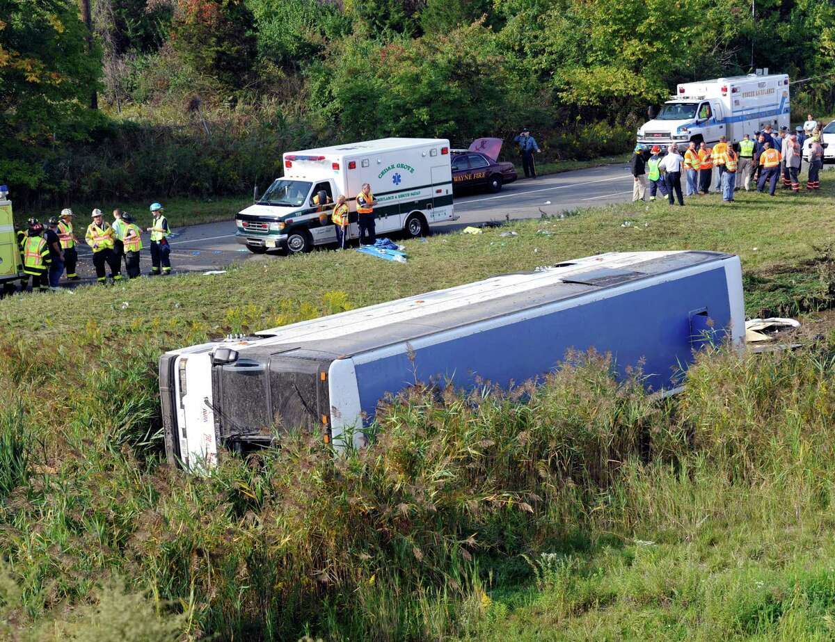 Rescue workers stand by after a bus overturned in a ditch at an exit ramp off Route 80 in Wayne, N.J. Saturday, Oct. 6, 2012. The chartered tour bus from Toronto carrying about 60 people overturned on an interstate exit ramp. Three people have been taken to hospital with non-life-threatening injuries. (AP Photo/Bill Kostroun)