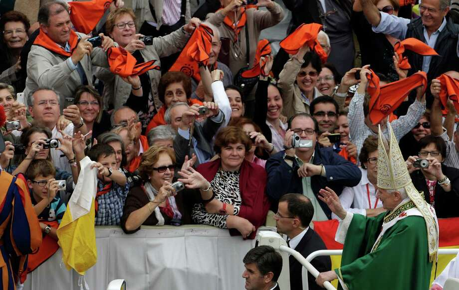 "Pope Benedict XVI waves to faithful as he is leaves after celebrating a mass for the opening of the synod of bishops in St. Peter's Square, at the Vatican, Sunday, Oct. 7 , 2012. Pope Benedict XVI has also named two new ""doctors"" of the church, conferring the Catholic Church's highest honor on a 16th-century Spanish preacher St. John of Avila, and  to St. Hildegard of Bingen, and a 12th— century German mystic who wasn't even officially recognized as a saint until earlier this year. Photo: Alessandra Tarantino / AP"