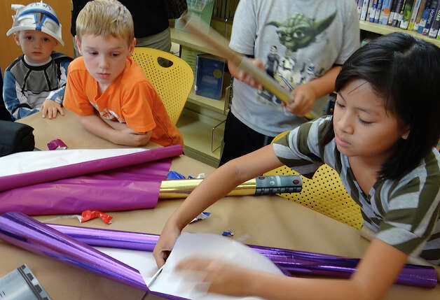 Kids make light sabres from cardboard tubes and shiny wrapping paper at Fairfield Public Library's Star Wars Reads Day on Saturday. Photo: Mike Lauterborn / Fairfield Citizen contributed