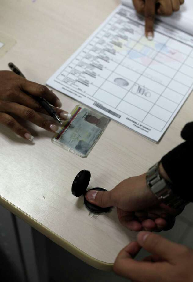 A voter inks his thumb as part of the voting process during the presidential election at a polling station in Caracas, Venezuela, Sunday, Oct. 7, 2012.  President Hugo Chavez is running against opposition candidate Henrique Capriles. Photo: Ramon Espinosa