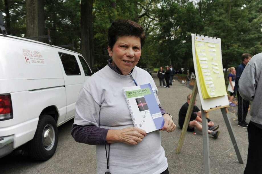 John Zumbo's mother Providence holds the fitness book that John was writing before he died in a car accident in 2006 at the seventh John Zumbo 5K Race in Bruce Park Sunday, Oct. 7, 2012. The book would be finished posthumously. The race benefits the John D. Zumbo Memorial Scholarship Fund, which provides scholarships to Greenwich High School graduates who plan to go to college and study in the health or fitness field. Photo: Helen Neafsey / Greenwich Time