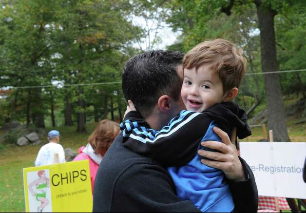Dave Matterazzo, of Greenwich, holds his son James, 2, at the seventh John Zumbo 5K Race in Bruce Park Sunday, Oct. 7, 2012. The race benefits the John D. Zumbo Memorial Scholarship Fund, which provides scholarships to Greenwich High School graduates who plan to go to college and study in the health or fitness field. Photo: Helen Neafsey / Greenwich Time