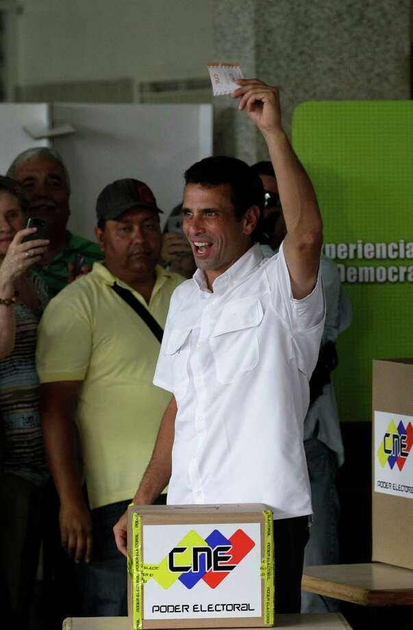 Opposition presidential candidate Henrique Capriles holds up his ballot as he votes in the presidential election in Caracas, Venezuela, Sunday, Oct. 7, 2012. Capriles is running against President Hugo Chavez. Photo: Ariana Cubillos