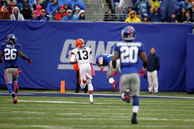 Cleveland Browns wide receiver Josh Gordon (13) runs away from New York Giants free safety Antrel Rolle (26) and  Prince Amukamara (20) for a touchdown during the first half of an NFL football game Sunday, Oct. 7, 2012, in East Rutherford, N.J. (AP Photo/Julio Cortez) Photo: Julio Cortez / AP