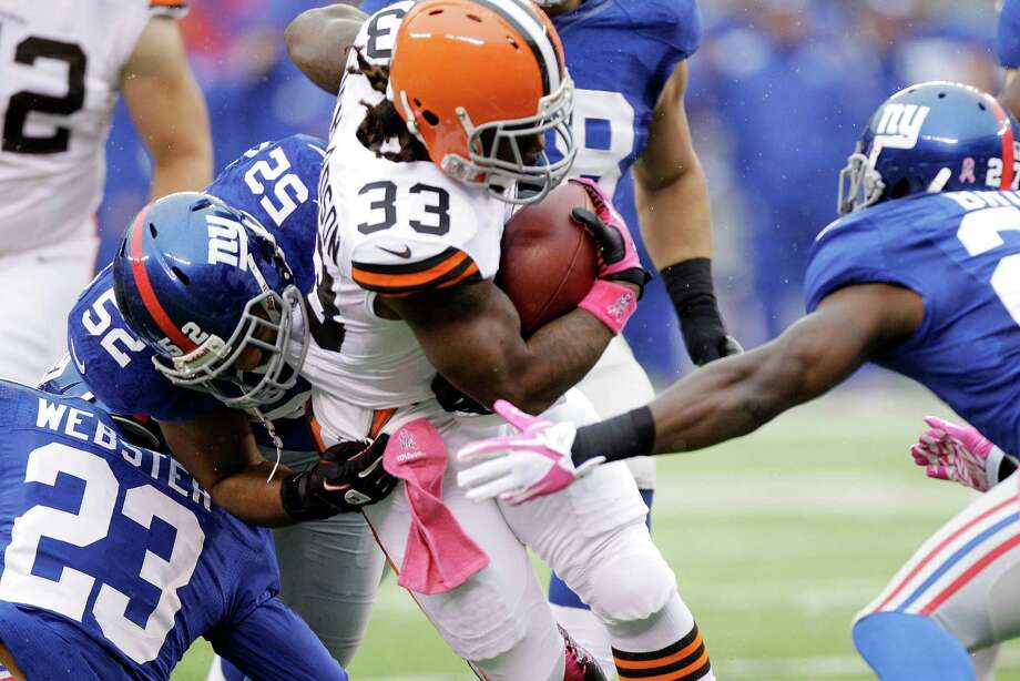 Cleveland Browns running back Trent Richardson (33) is tackled by New York Giants linebacker Spencer Paysinger (52) and Corey Webster  (23) during the first half of an NFL football game Sunday, Oct. 7, 2012, in East Rutherford, N.J. (AP Photo/Kathy Willens) Photo: Kathy Willens / AP