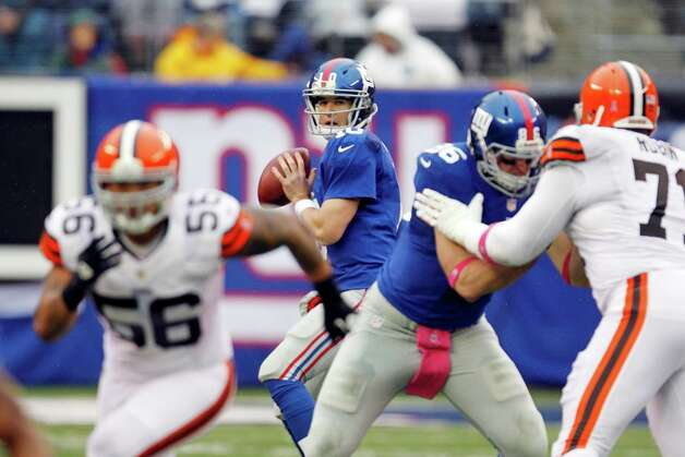 New York Giants quarterback Eli Manning (10) looks to pass as tight end Bear Pascoe (86) blocks for him during the first half of an NFL football game against the Cleveland Browns Sunday, Oct. 7, 2012, in East Rutherford, N.J. (AP Photo/Julio Cortez) Photo: Julio Cortez / AP