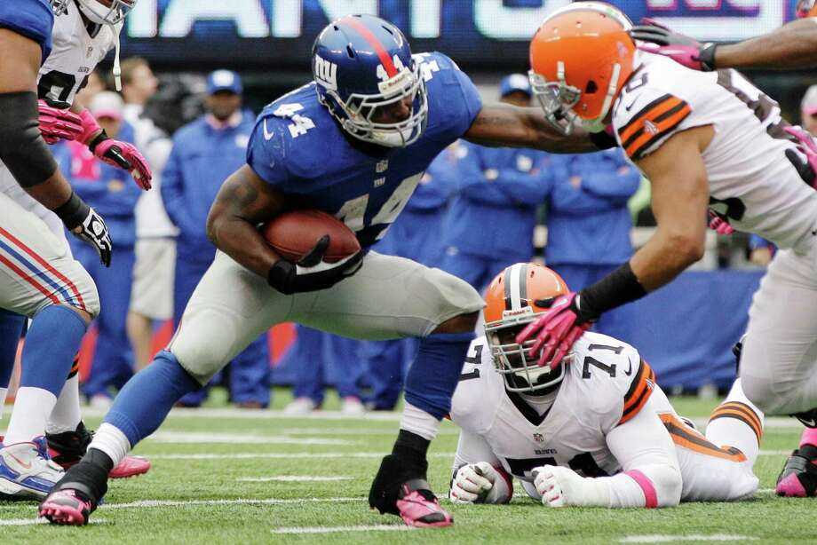 Cleveland Browns linebacker Marcus Benard, right, tackles New York Giants running back Ahmad Bradshaw (44) during the first half of an NFL football game Sunday, Oct. 7, 2012, in East Rutherford, N.J. (AP Photo/Kathy Willens) Photo: Kathy Willens / AP