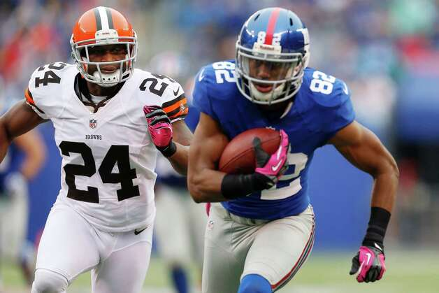 New York Giants wide receiver Rueben Randle (82) runs away from Cleveland Browns cornerback Sheldon Brown (24) during the first half of an NFL football game Sunday, Oct. 7, 2012, in East Rutherford, N.J. (AP Photo/Julio Cortez) Photo: Julio Cortez / AP