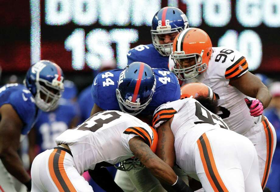 Cleveland Browns strong safety T.J. Ward (43) and  John Hughes (93) hit New York Giants running back Ahmad Bradshaw (44) during the first half of an NFL football game Sunday, Oct. 7, 2012, in East Rutherford, N.J. (AP Photo/Kathy Willens) Photo: Kathy Willens / AP