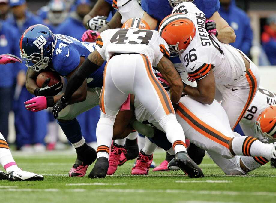 New York Giants running back Ahmad Bradshaw (44) is tackled by Cleveland Browns' T.J. Ward (43) and teammate  Emmanuel Stephens during the first half of an NFL football game Sunday, Oct. 7, 2012, in East Rutherford, N.J. (AP Photo/Kathy Willens) Photo: Kathy Willens / AP